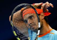 Rafael Nadal of Spain adjusts his headband during his match against France's Pierre-Hugues Herbert at the Swiss Indoors ATP tennis tournament in Basel October 22, 2014. REUTERS/Arnd Wiegmann