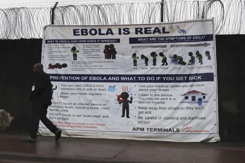 A man walks by a sign that reads ''Ebola is real'' in Monrovia, Liberia, October 21, 2014. REUTERS/James Giahyue