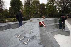 People rest at a monument to thousands of Austrians who deserted Hitler's army during World War Two in Vienna October 24, 2014. REUTERS/Heinz-Peter Bader