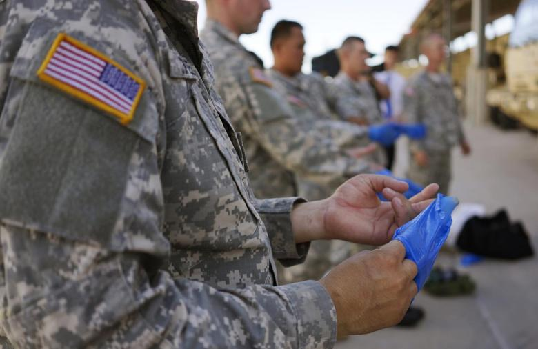 Soldiers from the U.S. Army 615th Engineer Company, 52nd Engineer Battalion practise the proper way to remove protective gloves during the final session of personal protective equipment training at Ft. Carson in Colorado Springs, Colorado October 23, 2014. REUTERS/Rick Wilking