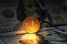 Монета 10 рублей и банкноты 100 долларов США в Санкт-Петербурге 22 октября 2014 года. Рубль дешевеет в понедельник из-за локального спроса на валюту в условиях её дефицита на фоне западных санкций, переписывая минимумы и быстро отыграв подтверждение инвестиционного рейтинга России агентством S&P. REUTERS/Alexander Demianchuk