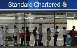 Очередь в отделение банка Standard Chartered в Сингапуре 23 января 2014 года. Операционная прибыль Standard Chartered Plc в третьем квартале 2014 года снизилась на 16 процентов в результате роста расходов, связанных с реструктуризацией южнокорейского бизнеса банка, и увеличения объема невозвратных кредитов. REUTERS/Edgar Su
