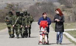 """Вооруженные люди, предположительно российские военнослужащие, и местные жители близ Симферополя 14 марта 2014 года. Россия не представляет прямой военной угрозы Евросоюзу, но ее вторжение на Украину относится к типу """"гибридной войны"""", с которой, как сказал в понедельник министр иностранных дел Дании, Европа должна бороться, используя скоординированную энергетическую политику и прессу, чтобы противостоять """"массированной пропаганде"""". REUTERS/Vasily Fedosenko"""