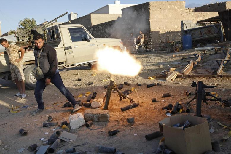 A fighter from armed group Operation Dawn fires a mortar during clashes with rival group the Zintan brigade, on the outskirts of the city of Kklh, southwest of Tripoli October 21, 2014. REUTERS/Ismail Zitouny