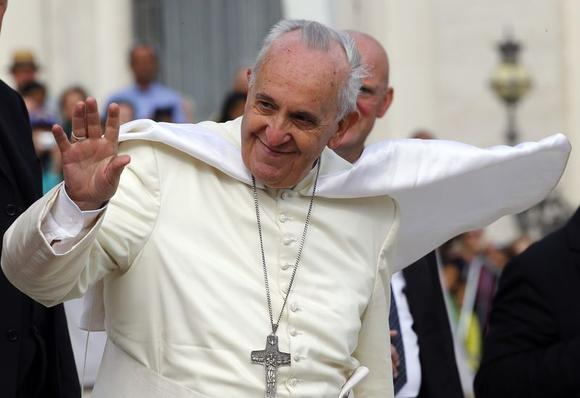A gust of wind blows Pope Francis' mantle as he leaves at the end of his weekly audience in Saint Peter's Square at the Vatican October 22, 2014. REUTERS/Stefano Rellandini