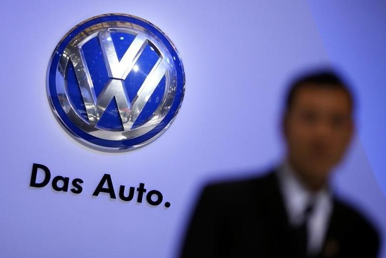 A security guard stand next to a Volkswagen logo at the stage of the company prior to the opening of the 15th Shanghai International Automobile Industry Exhibition April 19, 2013.  REUTERS/Carlos Barria
