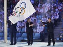 Prefeito de Pyeongchang, Lee Sok-ra, ergue a bandeira olímpica ao lado do presidente do COI, Thomas Bach, durante cerimônia de encerramento da Olimpíada de Inverno de Sochi 2014, na Rússia. 23/02/2014. REUTERS/Gary Hershorn