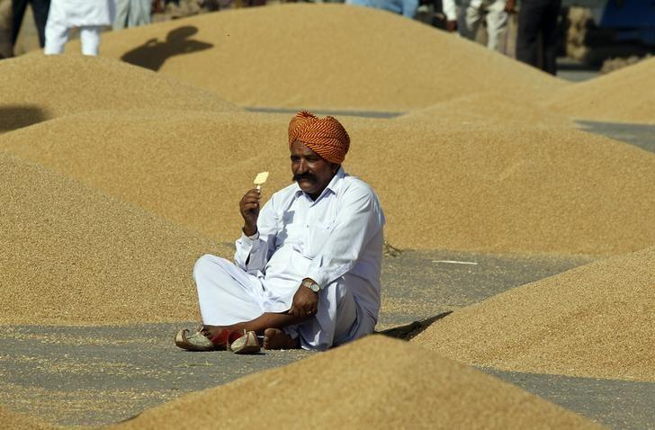 A farmer eats an ice-cream as he waits to procure his wheat crop at a wholesale grain market in the northern Indian city of Chandigarh April 26, 2014. REUTERS/Ajay Verma/Files