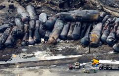 A firefighter stands close to the remains of a train wreckage in Lac Megantic in this file photo from July 8, 2013.  REUTERS/Mathieu Belanger/Files