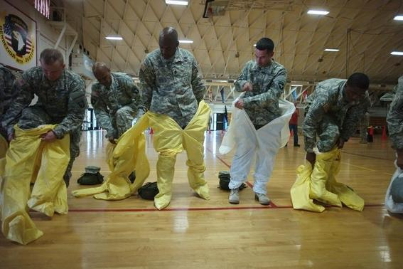 Soldiers wearing protective suits as US Army soldiers from the 101st Airborne Division (Air Assault), who are earmarked for the fight against Ebola, conduct training before their deployment to West Africa, at Fort Campbell, Kentucky October 9, 2014. REUTERS/Harrison McClary