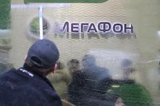 Мужчина моет окно в салоне продаж Мегафона в Москве 28 ноября 2012 года. Чистая прибыль второго по доле рынка телекоммуникационного оператора России Мегафона в третьем квартале 2014 года снизилась в годовом выражении на 16,5 процента, оказавшись чуть лучше ожиданий аналитиков, а выручка выросла на 4,5 процента, сообщила компания в четверг. REUTERS/Sergei Karpukhin