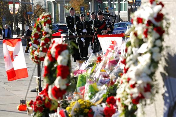 The day's first posting of the sentries, framed by flowers and wreaths left in tribute to Cpl. Nathan Cirillo, arrive at the National War Memorial in Ottawa October 30, 2014.   REUTERS/Chris Wattie