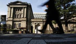 Люди проходят мимо здания Банка Японии в Токио 31 октября 2013 года. Банк Японии удивил мировые финансовые рынки в пятницу, расширив программу монетарного смягчения, так как экономический рост и инфляция не оправдывают прогнозов после повышения налога с продаж в апреле. REUTERS/Yuya Shino