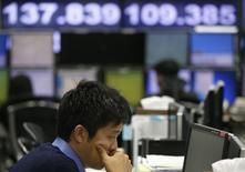 Un trabajador de un compañía operadora de cambios frente a un monitor que muestra el yen japonés versus el dólar en Tokio, 31 octubre, 2014.Las acciones japonesas anotaron el viernes su máximo de cierre desde noviembre del 2007 y el yen cayó a mínimos en casi siete años contra el dólar después de que el Banco de Japón sorprendió a los mercados con nuevas medidas de flexibilización que describió como una medida preventiva para acelerar la inflación.  REUTERS/Toru Hanai