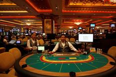Croupiers sit in front of gaming tables inside a casino on the opening day of Sands Cotai Central, Sands' newest integrated resort in Macau in this April 11, 2012 file photograph.  REUTERS/Tyrone Siu/Files