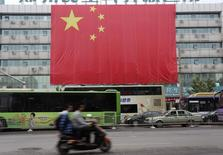 Residents ride their electric scooter past a giant Chinese national flag to mark the 65th anniversary of the founding of the People's Republic of China, in Zhengzhou, Henan province October 1, 2014. REUTERS/Stringer