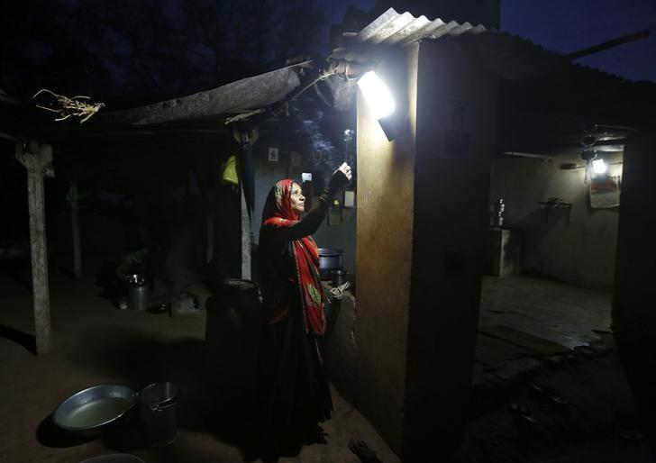 A woman holds an incense stick as she prays in front of a Compact Fluorescent Lamp (CFL) powered by solar energy, in her house, on the outskirts of Ahmedabad October 27, 2014.  REUTERS/Amit Dave
