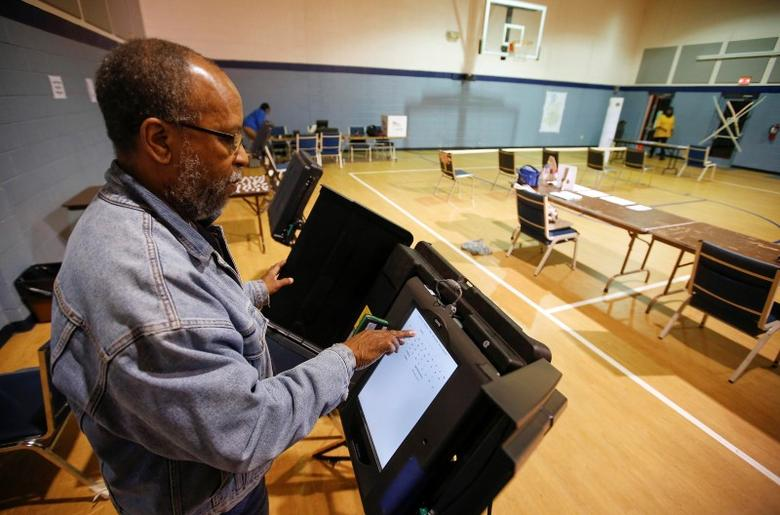 Poll worker Willie Stafford Jr. programs a voting terminal before the start of the voting at the Grove Presbyterian Church in Charlotte, North Carolina November 4, 2014. REUTERS/Chris Keane