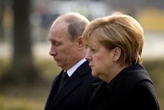 Президент России Владимир Путин и канцлер Германии Ангела Меркель возлагают венки на кладбище в Ганновере 8 апреля 2013 года. Канцлер Германии Ангела Меркель заявила в среду, что Европа не собирается облегчать бремя экономических санкций для России, наложенных из-за украинского кризиса, и устроенное пророссийскими сепаратистами в воскресенье голосование лишь укрепило решимость европейцев. REUTERS/Odd Andersen/Pool