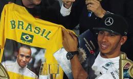 Lewis Hamilton segura camisa do Brasil durante entrevista em São Paulo nesta quarta-feira. REUTERS/Paulo Whitaker