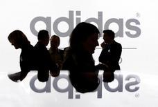 Акционеры Adidas Group на фоне логотипа компании перед началом общего собрания акционеров в Фюрте 8 мая 2008 года. Немецкий производитель спорттоваров Adidas AG сообщил в четверг, что ждет замедления роста продаж в 2015 году, и опубликовал финансовые результаты за третий квартал, совпавшие с прогнозом рынка. REUTERS/Michaela Rehle