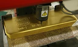 Слиток золота в процессе нанесения гравировки на заводе Красцветмет в Красноярске 27 февраля 2014 года. Золотовалютные резервы РФ достигли минимальных значений с октября 2009 года, потеряв за неделю $10,5 миллиарда, в основном, из-за валютных интервенций Центробанка. REUTERS/Ilya Naymushin
