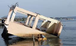 Meninos em barco improvisado com restos de refrigerador perto de casa destruída pelo tufão Haiyan, na cidade de Tacloban (Filipinas). 5/11/2014   REUTERS/Erik De Castro