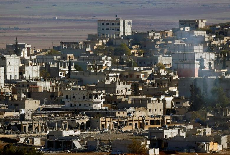 An Islamic State flag flies atop a building on the east side of the badly damaged Syrian town of Kobani during fighting between Islamic state forces and Kurdish fighters on November 6, 2014. REUTERS/Yannis Behrakis