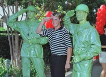 """Jovem posa com dois """"soldadinhos verdes de plástico"""" do filme Toy Story em parque da Disney. REUTERS/Arquivo"""
