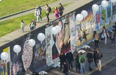 People walk under stands with balloons placed along the former Berlin Wall location at East Side Gallery, which will be used in the installation 'Lichtgrenze' (Border of Light) in Berlin November 7, 2014. REUTERS/Hannibal