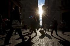 Personas transitan por la mañana en el distrito financiero de Wall Street en Nueva York. Imagen de archivo, 30 octubre, 2014. El crecimiento del empleo en Estados Unidos se mantuvo a un ritmo fuerte en octubre mientras que la tasa de desocupación bajó a un nuevo mínimo en seis años de 5,8 por ciento, subrayando la resistencia de la economía de cara a la desaceleración de la demanda global. REUTERS/Brendan McDermid
