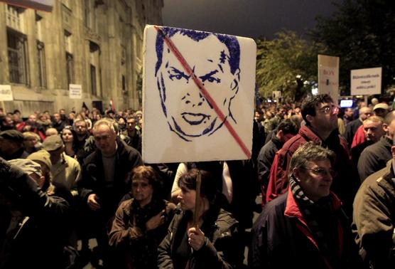 A woman carries a placard with the likeness of Hungary's Prime Minister Viktor Orban as thousands of Hungarians protest against perceived corruption at the country's tax authority and lack of wider democratic freedoms, in Budapest, November 9, 2014. REUTERS-Bernadett Szabo