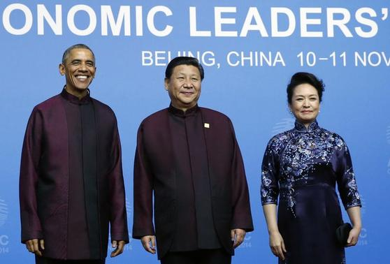 U.S. President Barack Obama (L) poses for photographs with China's President Xi Jinping (C) and Xi's wife Peng Liyuan during the APEC Welcome Banquet at Beijing National Aquatics Center, or the Water Cube, in Beijing, November 10, 2014. REUTERS-Kim Kyung-Hoon