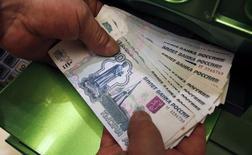 Мужчина держит в руках рублевые купюры у банкомата в отделении Сбербанка в Санкт-Петербурге 5 ноября 2014 года. Рубль значительно вырос после словесных интервенций руководства страны в понедельник, когда Центробанк открыл новую страницу в истории валютного рынка, отказавшись от коридора и регулярных интервенций, что в целом снижает спекулятивное давление на рубль, сохраняя риски повышенной волатильности. REUTERS/Alexander Demianchuk