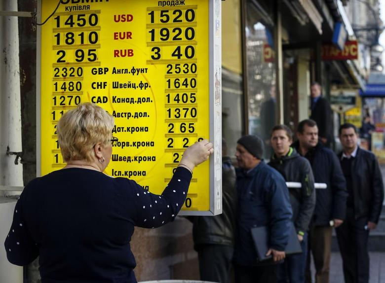 An exchange office worker changes numbers indicating the conversion rates outside a currency exchange office in central Kiev November 10, 2014.  REUTERS/Gleb Garanich