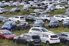 Автомобили на парковке дилерского центра на окраине Москвы 18 августа 2014 года. В октябре 2014 года авторынок РФ замедлил падение, сократившись лишь на 9,9 процента до 211.365 штук, сообщила в среду Ассоциация европейского бизнеса (АЕБ). REUTERS/Maxim Zmeyev
