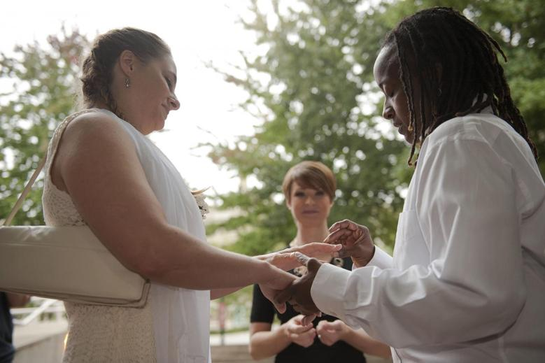 Kathy Stewart (R) places a ring on the finger of her partner, Vicky Mangus (L), during a wedding ceremony outside of the Mecklenburg County Register of Deeds office in Charlotte, North Carolina, October 13, 2014. REUTERS/Davis Turner