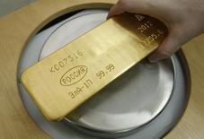 """Работник красноярского завода Красцветмет взвешивает слиток золота 12 апреля 2012 года. Золотовалютные резервы РФ достигли минимальных значений с начала октября 2009 года, потеряв за неделю $7,2 миллиарда, в основном, из-за возврата Центробанком валюты в рамках операций """"валютный своп"""", а также отрицательной переоценки валют и золота. REUTERS/Ilya Naymushin"""