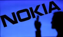 Fotografía de la silueta de una persona frente al logo de Nokia. Imagen de archivo, 23 enero, 2014. La compañía de telecomunicaciones finlandesa Nokia elevó el viernes su objetivo de rentabilidad a largo plazo gracias a la fuerte demanda de este año por redes 4G más rápidas, y dijo que también espera que el negocio crezca en 2015. REUTERS/Dado Ruvic