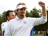 European Ryder Cup player Victor Dubuisson celebrates as he stands with teammate Graeme McDowell (rear) on the 14th hole after winning their foursomes 40th Ryder Cup match at Gleneagles in Scotland September 27, 2014. REUTERS/Eddie Keogh