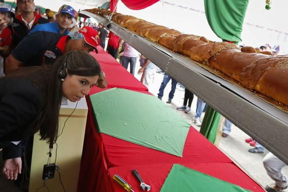 Kim Partrick (L), a representative of the Guinness World Records, examines a giant ham bread, a typical Venezuelan Christmas dish, during an attempt to break the Guinness World Record for the biggest ham bread, in Caracas November 15, 2014. REUTERS/Carlos Garcia Rawlins