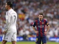 "Barcelona's Lionel Messi (R) reacts as Real Madrid's Cristiano Ronaldo walks during their Spanish first division ""Clasico"" soccer match at the Santiago Bernabeu stadium in Madrid October 25, 2014.      REUTERS/Juan Medina"