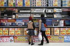 Gente observa computadoras del escaparate de una tienda de electrónica en Tokio. 16 de noviembre de 2014. La economía de Japón cayó inesperadamente en recesión en el tercer trimestre, lo que llevaría al primer ministro Shinzo Abe a retrasar un impopular aumento de impuestos a las ventas y a convocar a elecciones anticipadas a sólo dos años de haber asumido el poder. REUTERS/Yuya Shino