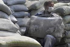 Рабочий носит мешки с цементом на строительном рынке в городе Хэфэй 2 июня 2010 года. Китайская Gansu Shangfeng Cement в понедельник оценила в $114 миллионов планируемые вложения в Киргизии, где собирается выпускать стройматериалы. REUTERS/Stringer