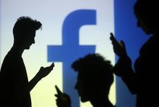 Pessoas checam seus telefones com o logo do Facebook ao fundo, em Zenica, na Bósnia. 29/11/2014. REUTERS/Dado Ruvic
