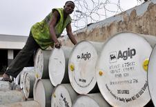 """Un hombre ordena unos tambores con petróleo en una gasolinera y depósito en Abuya, jun 19 2009. La caída de los precios del petróleo y de otras materias primas, junto a la perspectiva de un alza en las tasas de interés a nivel global, amenazan con devolver a algunos de los mayores mercados emergentes a niveles de crédito """"basura"""", destapando la incapacidad de muchos países de impulsar reformas durante el auge. REUTERS/Afolabi Sotunde"""