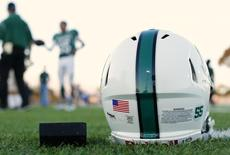 A football helmet's health warning sticker is pictured between a U.S. flag and the number 55, in memory of former NFL player Junior Seau in Oceanside, California September 14, 2012.   REUTERS/Mike Blake