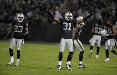 Nov 20, 2014; Oakland, CA, USA; Oakland Raiders cornerback Neiko Thorpe (31) and Tarell Brown (23) celebrate after the game against the Kansas City Chiefs at O.co Coliseum. Kirby Lee-USA TODAY Sports