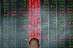 An investor reacts in front of an electronic board showing stock information at a brokerage house in Taiyuan, Shanxi province, May 9, 2013.  REUTERS/Jon Woo