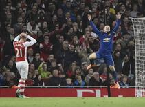 Manchester United's Wayne Rooney (R) celebrates an own goal by Arsenal's Kieran Gibbs during their English Premier League soccer match at the Emirates Stadium in London November 22, 2014. REUTERS/Toby Melville